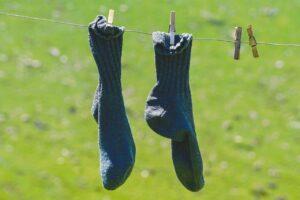 Et par blå sokker hænger til tørre på tørrestativ