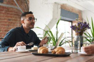 Mand taler med anden i mens hans spiser