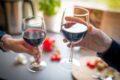 To personer skåler i rødvin